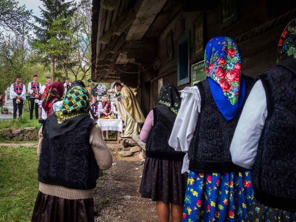 People dressed in traditional costumes attending church in Maramures, Romania